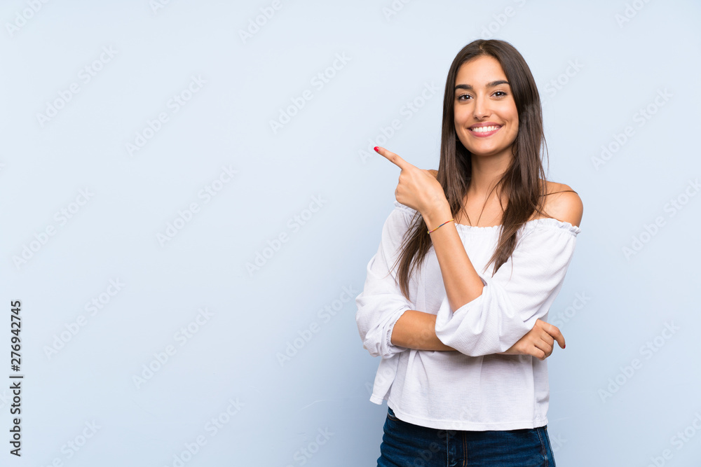 Fototapeta Young woman over isolated blue background pointing finger to the side