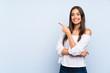 Leinwandbild Motiv Young woman over isolated blue background pointing finger to the side