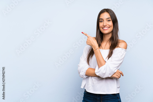 Obraz Young woman over isolated blue background pointing finger to the side - fototapety do salonu