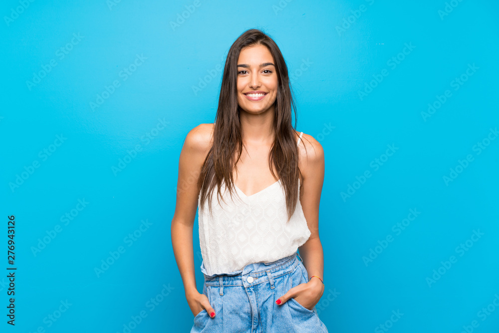 Fototapeta Young woman over isolated blue background laughing