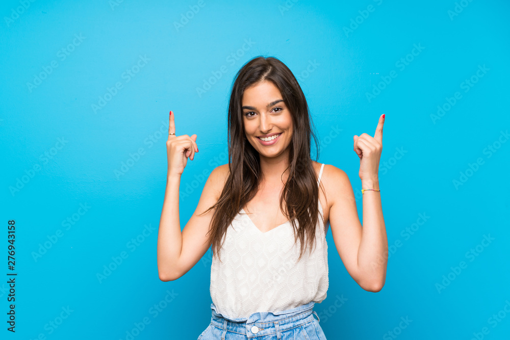 Fototapeta Young woman over isolated blue background pointing up a great idea