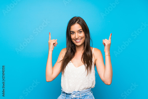Obraz Young woman over isolated blue background pointing up a great idea - fototapety do salonu
