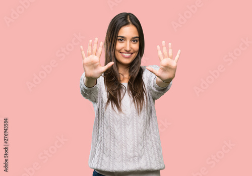 Fényképezés  Young hispanic brunette woman counting ten with fingers over isolated background