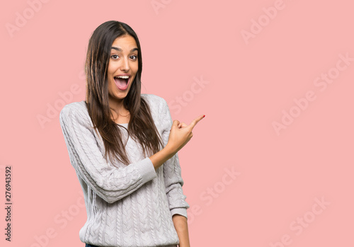 Young hispanic brunette woman surprised and pointing side over isolated backgrou Slika na platnu