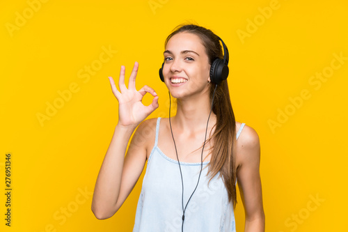 Obraz na plátně  Young woman listening music over isolated yellow wall showing ok sign with finge