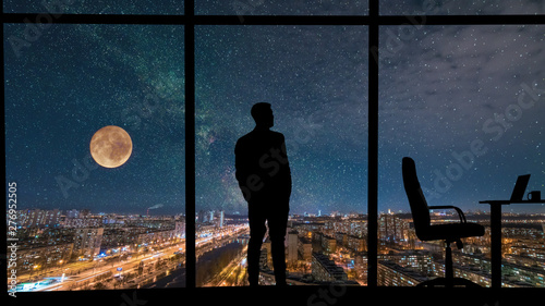 Fotografia The man standing near the panoramic window on city with starry sky background