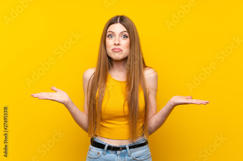 Pinturas sobre lienzo  Young woman over isolated yellow background having doubts with confuse face expr