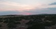 Wonderful valley with green hills under red sunset. Beauty drone footage of natural summer landscape and red sun shining in the evening.