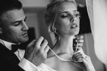 A Groom Is Putting A Necklace On A Bride's Neck. Black And White Image.