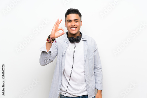 Fotografie, Obraz  Young man over isolated white wall with earphones showing ok sign with fingers