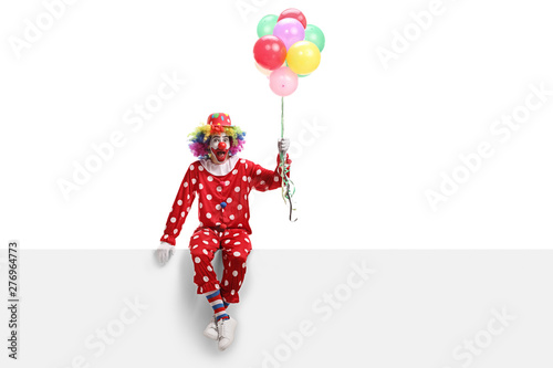 Stampa su Tela Cheerful clown sitting on a white banner and holding a bunch of balloons
