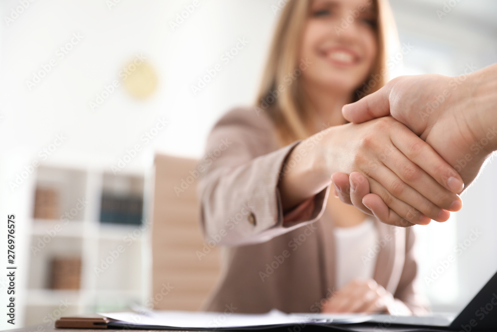 Fototapeta Business partners shaking hands at table after meeting, closeup. Space for text