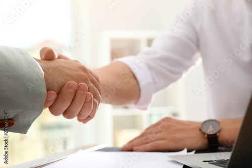 Photo Business partners shaking hands at table after meeting in office, closeup