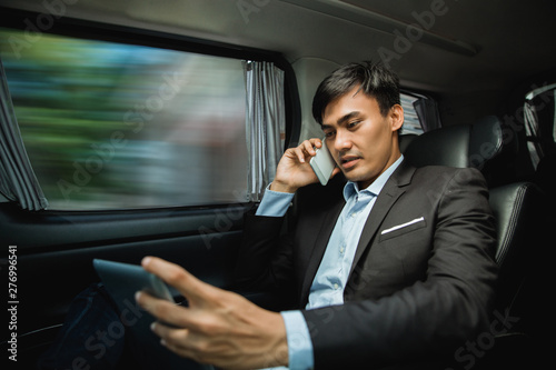 Carta da parati busy asian businessman calling by phone and using tablet on his way to meeting w