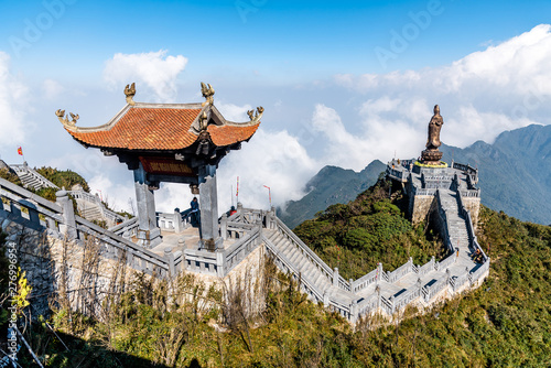 Foto  SAPA, VIETNAM - MAR 14, 2019 Statue of the Guan-Yin Buddha and Pavilion on Fansipan mountain peak the highest mountain in Indochina Backdrop Beautiful view blue sky and cloud