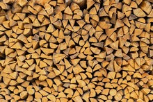 Texture Of An End Face Of Wooden Firewood In A Stack For A Background Or For Wallpaper.