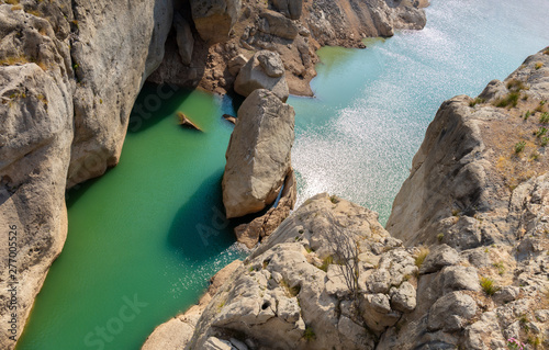 Dangerously steep rock walls in an exciting gorge in the mountains of the Spanish province of Kastilla La Mancha. The water is turquoise green and sparkles in the sunlight.