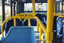 Sun Shines On Empty Interior Of London Double Decker Bus, Yellow Holding Rails And Blue Seats