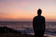 Silhouette Of A Man Against The Ocean At Sunset