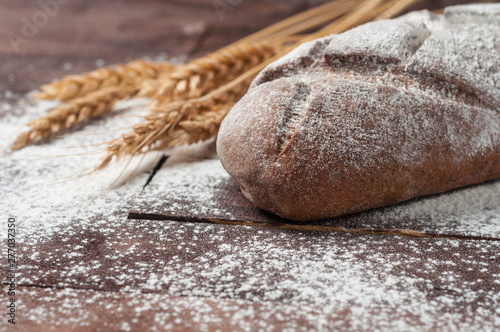 In de dag Brood Whole loaf of dark homemade bread sprinkled with flour near bunch of wheat lies on old brown boards