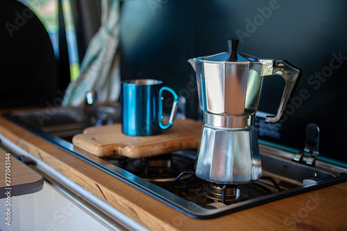 Aqua Bialetti stovetop coffee maker and mug, on a van gas cooker Fototapet