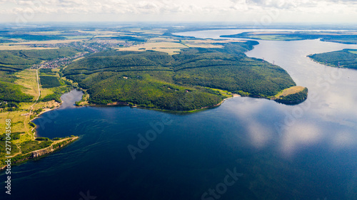 Fotografia  Aerial view from the drone of landscape Volga river flows among the hills and fields