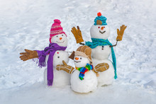 Funny Snowman Family In Stylish Hat And Scarf On Snowy Field. Happy Winter Time. Happy Funny Snowman In The Snow. Happy Smiling Snowman Group On Sunny Winter Day.