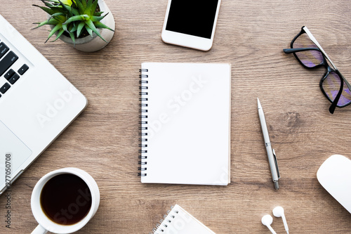 Obraz Blank notebook is on top of wood office desk table with lot of things on it. Top view, flat lay. - fototapety do salonu