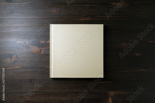 Blank square notebook or book on wooden background Fototapet