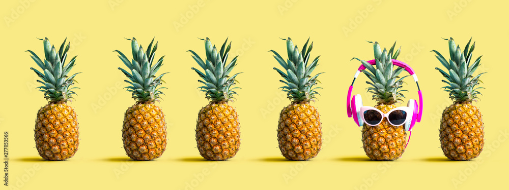 Fototapeta One out unique pineapple wearing headphones on a solid color background
