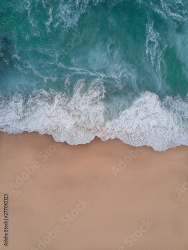 Aerial shot of beautiful splashing tall waves coming over the sandy beach
