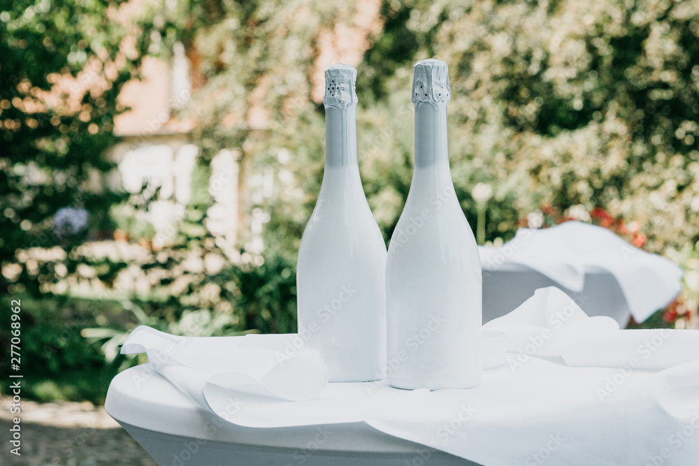 Fototapety, obrazy: Two white champagne bottles on the table. Festive concept.