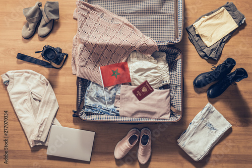 Fényképezés  Woman's clothes, laptop, camera, russian passport and flag of Morocco lying on the parquet floor near and in the open suitcase