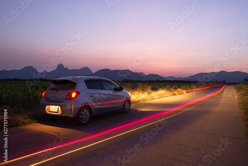 Foto auf AluDibond Flieder Travel car is parking at the road country side with landscape view beautiful sunset and light trails.