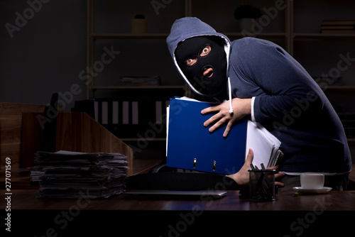 Cuadros en Lienzo Male thief in balaclava in the office night time