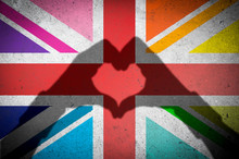 Hands Making Heart Shadow On Union Jack UK Flag With LGBTQI Gay Pride Rainbow Colored Panels On A Textured Grunge Concrete Wall Background