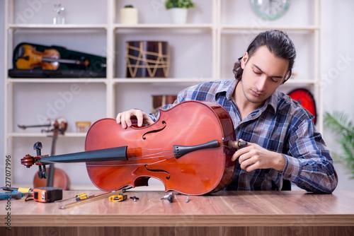 Young handsome repairman repairing violin - 277077996