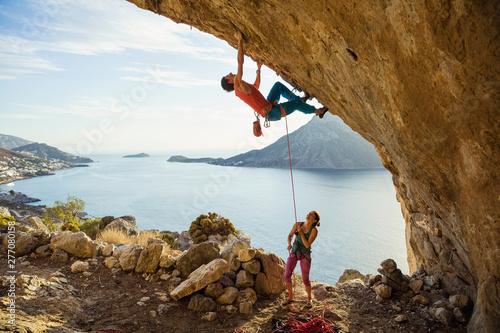 Fototapeta Young man starts climbing in cave, his female partner belaying him obraz