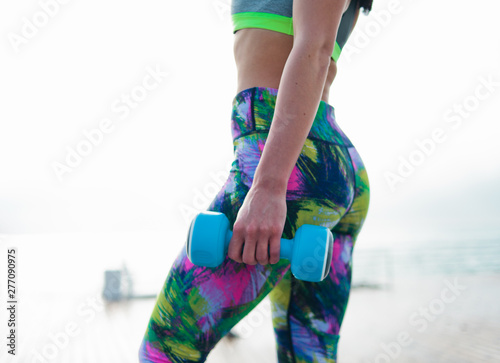 Aluminium Prints Magic world Young fit woman in sportswear posing with dumbbells in her hands at the morning on sunrise beach