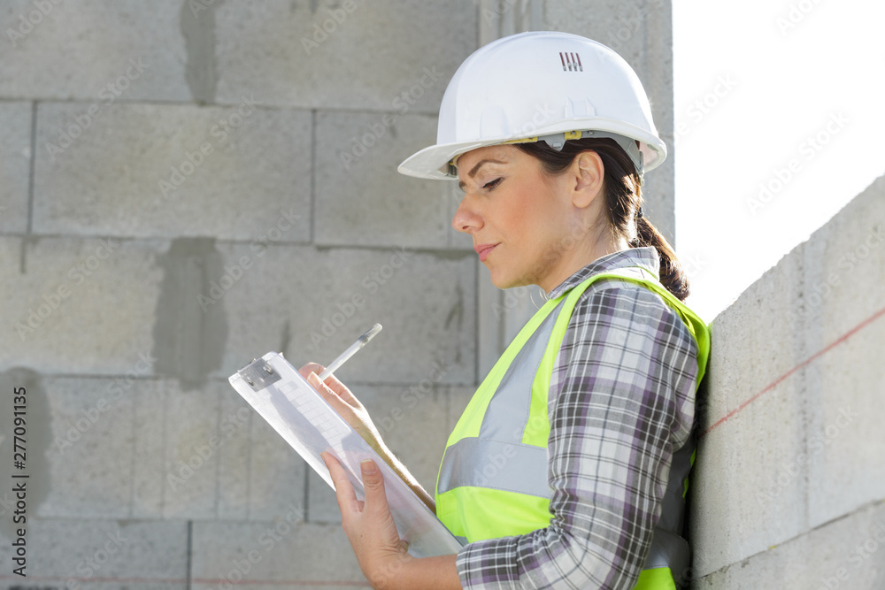 Fototapety, obrazy: woman builder holding blueprints clipboard