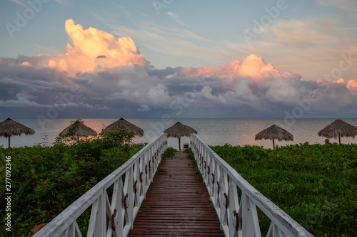 Beautiful view of a wooden path leading to the sandy beach on the Caribbean Sea in Cuba during a cloudy and rainy morning sunrise Wallpaper Mural