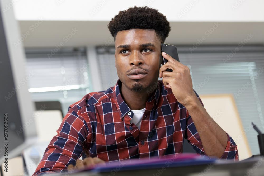 Fototapety, obrazy: consultant sat at desk having conversation on smartphone