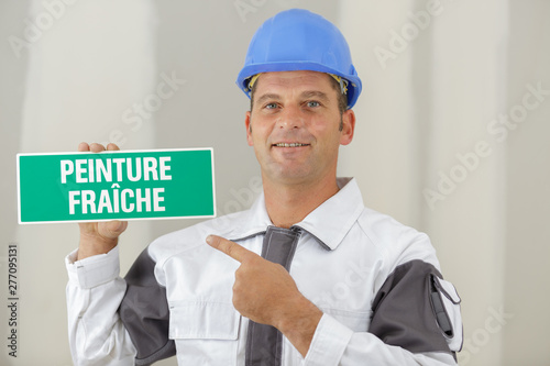 tradesman pointing to sign in french warning of wet paint Canvas Print