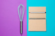 canvas print picture - Minimalism cooking concept. Recipe book, whisk on a blue-purple background.