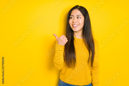 Beautiful brunette woman over yellow isolated background smiling with happy face looking and pointing to the side with thumb up.