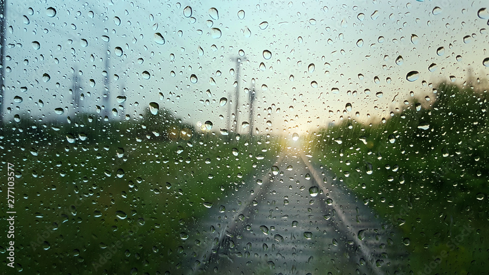 Fototapety, obrazy: Raindrops on a window with a blurred railway road background.