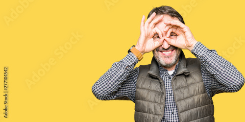 Fotomural  Middle age handsome man wearing winter vest doing ok gesture like binoculars sticking tongue out, eyes looking through fingers