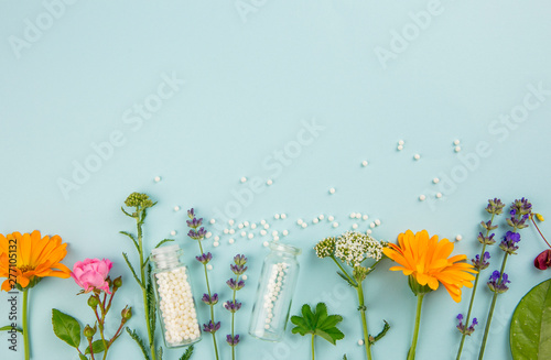 Flat lay view homeopathic medicine pills in jars and spilled around on light blue background, decorated with fresh various herbs and plants, flowers. Homeopathy border background, lot of copy space. - 277105132