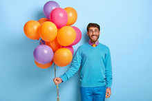 Happy Man Celebrates Anniversary Of Business Company, Comes On Corporate Party, Carries Colorful Air Balloons, Wears Glasses, Blue Neat Clothes Poses In Office. Cheerful Student Comes On Leaving Party