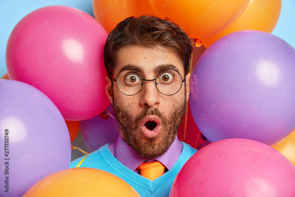 Fototapety, obrazy: Shocked party man wears optical spectacles, cannot believe eyes, being in stupor, reacts on holiday organisation, surrounded with colorful balloons. Festive event, emotions, human facial expressions